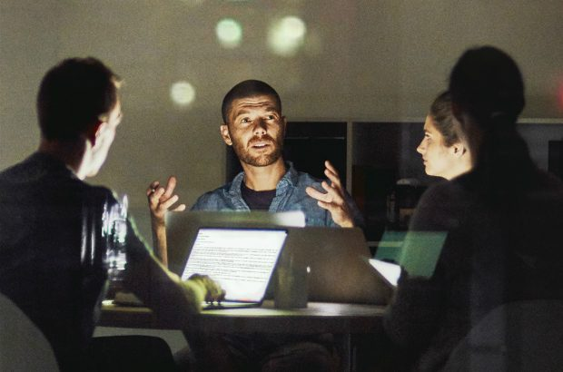 A business meeting at night illuminated by a laptop