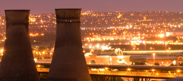 View of Sheffield at night with cooling towers in the foreground.
