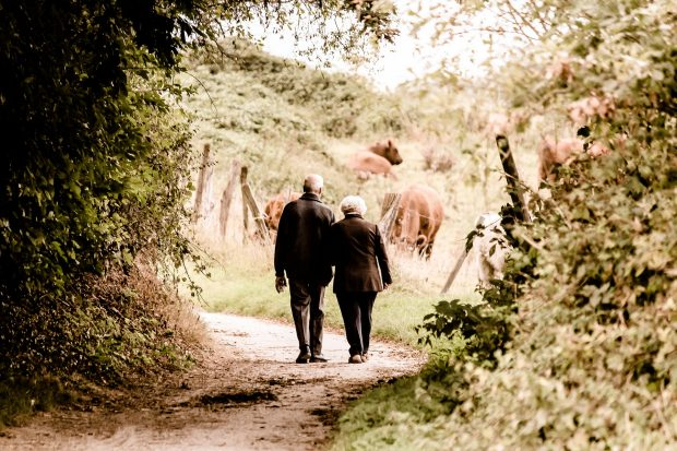 Older couple walking down a country path.
