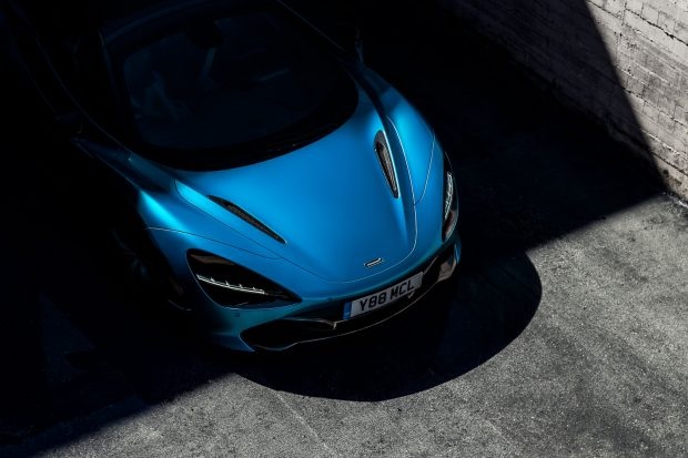 The front of a blue sportscar emerging from shadow.