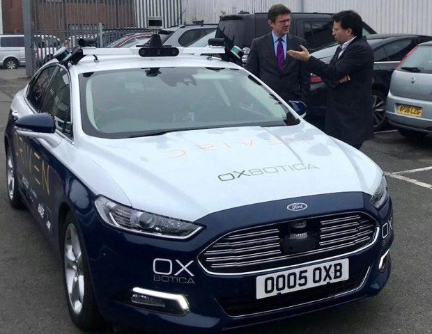 Greg Clark standing beside an Oxbotica car.