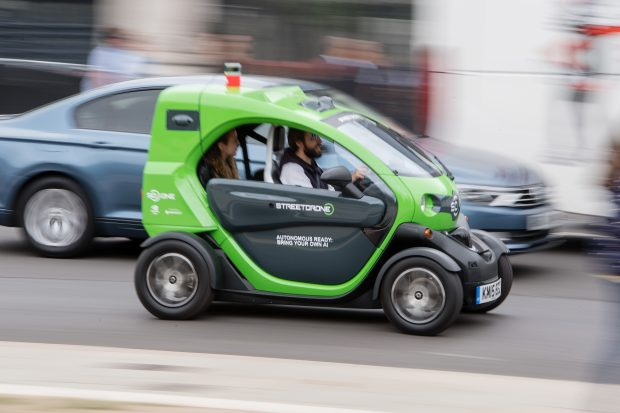 Small electric car speeding down a street.
