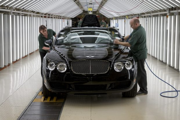 2 workers adding finishing touches to a Bentley car.