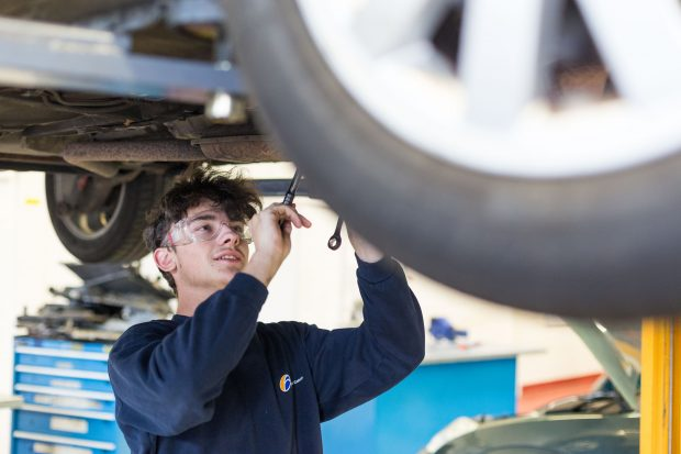 Student learning car maintenance