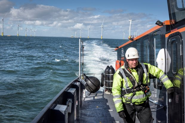 Man in high visibility clothing on a boat in front of an offshore wind farm.