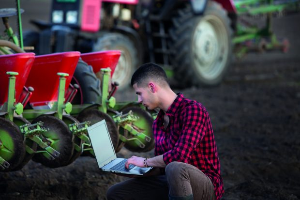 Farmer in a field with a laptop