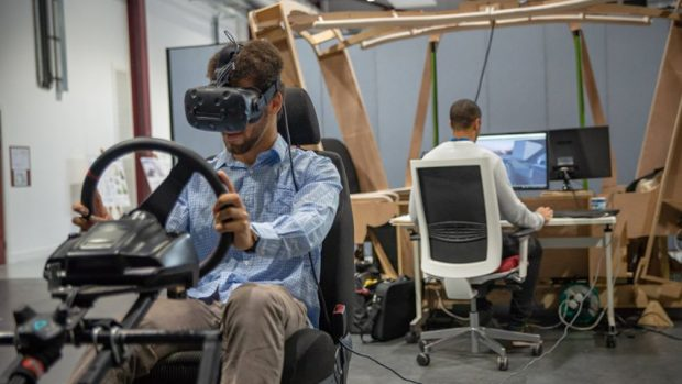Man test driving car wearing a virtual reality head set