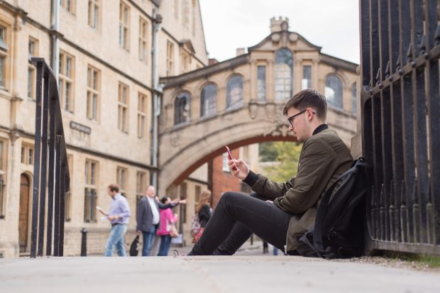 Man looking at phone with the Bridge of Sighs in the background